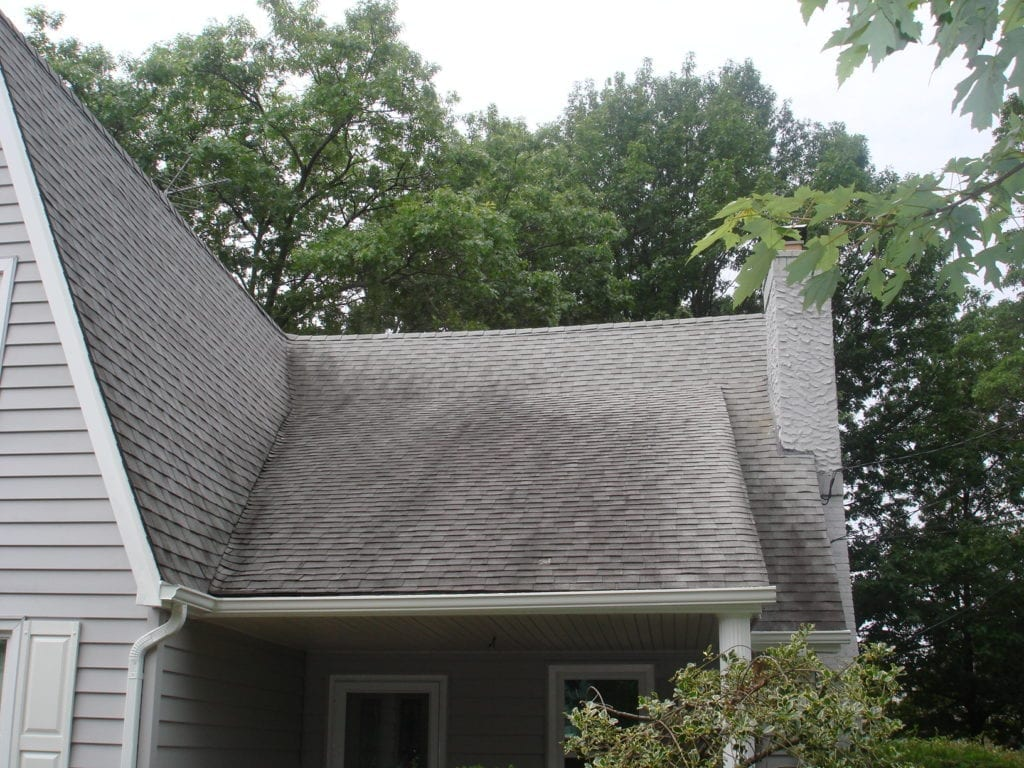 """SoftWash Low Pressure Roof Cleaning Don't replace your roof — restore it instead! Clean County provides professional roof cleaning services that protect the long life, curb appeal, and quality of your shingles. A Solution For Black Stains If you live in the Tri State area, it's likely that you've run into the """"black stain"""" issue on roofs. Many homes in the area have dark striped running down their shingles. The responsible party? A type of bacteria called Gloeocapsa Magma, which looks like algae and feeds on the limestone in your shingles. When Gloeocapsa Magma takes hold, it eats away at your roofing. This introduces issues like: Poor Curb Appeal Black stains don't exactly inspire a positive first impression. Even if the rest of your property is Martha Stewart Living-ready, it will be lost because of a dirty roof. Reduced Energy Efficiency The bacteria hurts your shingles' ability to fend off heat from the sun, which inflates cooling costs (especially during the summer). Shorter Roof Lifetime Without preventative care, your roof can't maintain its quality. This means that you're investing in a roof replacement long before you need to. The technicians at Clean County make it our job to take that dark, streaky, and algae-stained roof and turn it into something beautiful."""