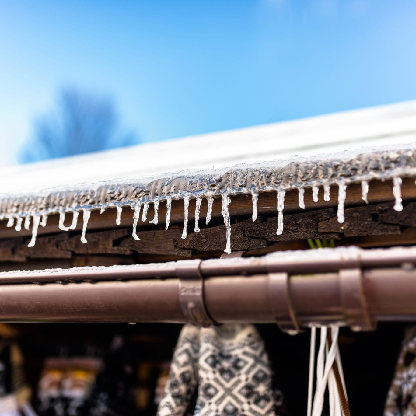 hanging-icicles-from-the-roof-of-a-wooden-building-GQPCP9X